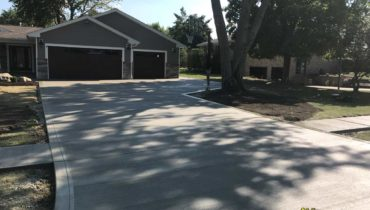 Concrete driveway installation with broom finish.